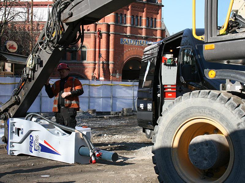 Servicetekniker skruvar på grävmaskin